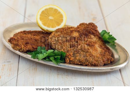 Plate of schnitzel with lemon and parsley on a wooden table.