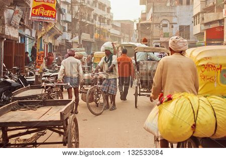 VARANASI, INDIA - JAN 1, 2016: Crowded street with cargo workers and cyclists driving through the old buildings of indian city on January 1, 2016. Varanasi urban agglomeration had a population of 1435113