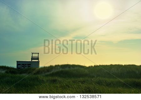 beach cafe at the sunset with nobody and green grass foreground. Baltic sea