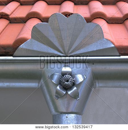 New decorative drainpipe on historical house on the roof