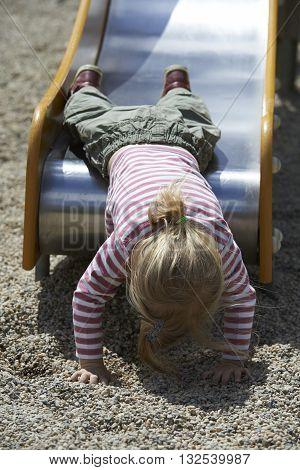 Cute little blond girl sliding on playground
