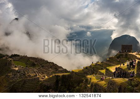 Machu Picchu Peru - September 7 2015: Machu Picchu illuminated by the first sunlight coming out from the opening clouds. The Inca's city is the most visited travel destination in Peru.
