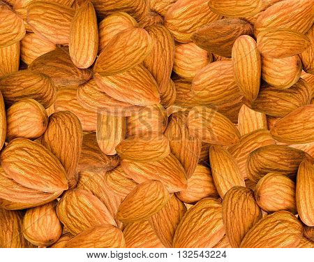 Big raw almonds background. Healthy nuts close up. Healthy food background. Fresh brown almonds. Vegetarian food nuts.
