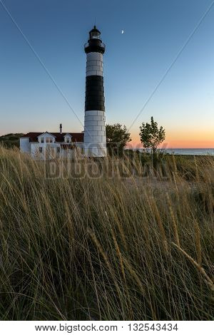 Moon over Big Sable Lighthouse along the shores of Lake Michigan at sunset.