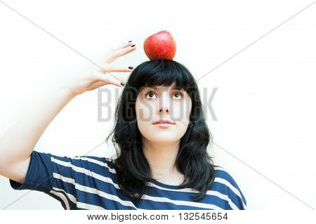 Pretty brunette girl with red apple on head isolated on white background