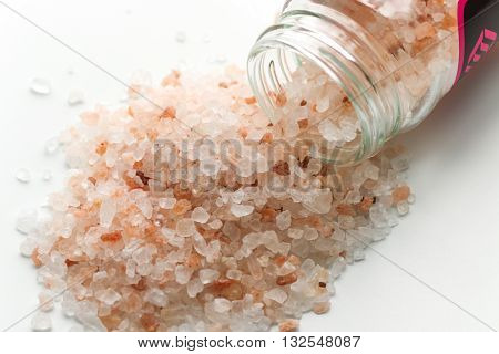 Himalayan pink salt in small jar of glass. Himalayan salt pile on white background. Pink crystal salt  isolated on white background. Close up Himalayan salt - pink and orange coarse crystals.