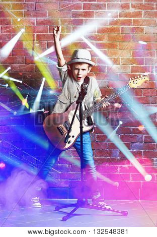 Little boy playing guitar, singing with microphone on laser rays and brick wall background