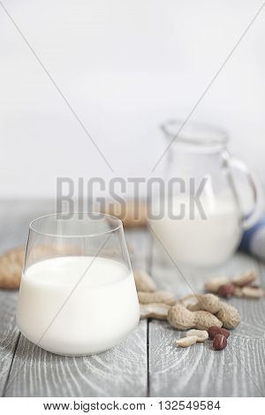 Milk with peanuts and pastry on a wodden board