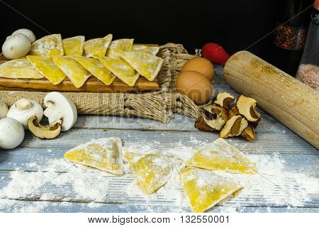 Making home made ravioli with porcini mushrooms on blue wooden table top