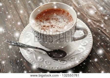 Vintage cup of cacao on wooden background with snow effect