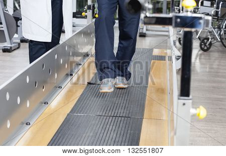 Low Section Of Senior Man Walking By Doctor