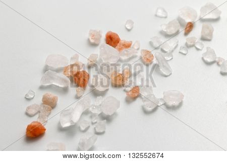 Pink Himalayan salt. Himalayan salt pile on white background. Pink crystal salt  isolated on white background. Close up Himalayan salt - pink and orange coarse crystals.