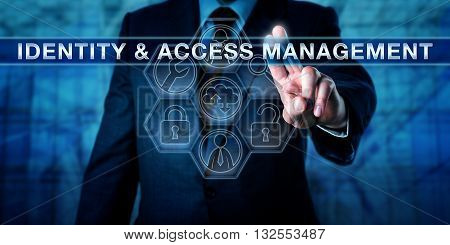 Manager pushing IDENTITY & ACCESS MANAGEMENT on a virtual interactive touch screen. Business metaphor and computer security procedure concept for technology enabling access to authenticated users.
