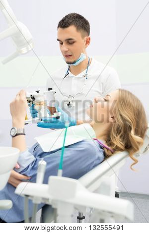 Cute girl in blue shirt and patient bib on the patient chair. She looks into a mirror in her left hand. Next to her there is a male dentist in a white uniform with blue latex gloves, blue mask and binocular loupes. He looks at the articulator with teeth m