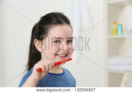 Smiling little girl brushing teeth, close up