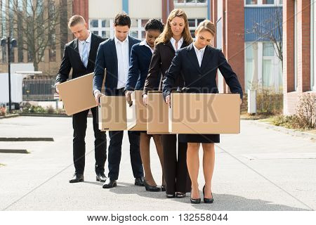 Group Of Unemployed Businesspeople With Cardboard Boxes Standing In A Line