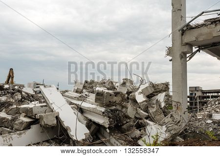 Demolition of large industrial buildings with piles of concrete parts