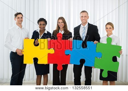 Group Of Businesspeople Holding Multi-colored Puzzle Pieces In Office