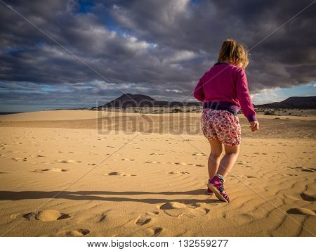 Little girl walking on the sand on the sand dunes in  the Natural Reserve of Dunes in Corralejo, Fuerteventura, Canary Islands, Spain