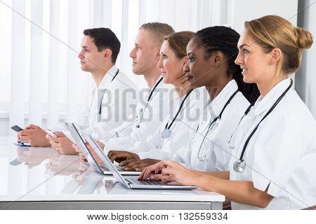 Group Of Multi-racial Doctors Using Laptop In Meeting