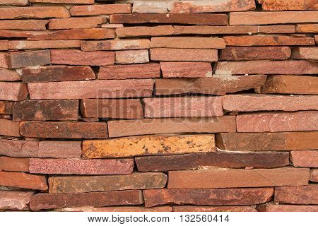 The wall of red stone. Decorative wall made of red stone.