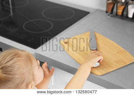 Little girl playing with knife in the kitchen