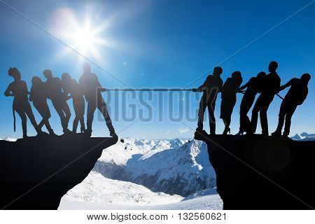 Silhouette Of People Playing Tug Of War On Cliff