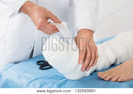 Close-up Of Doctor Hand Tying Bandage On The Leg Of Patient In Clinic