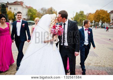 Newlyweds walking backgound bridesmaids and groomsman outdoor