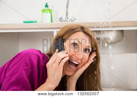 Close-up Of Woman Calling To Plumber While Water Leaking From Sink