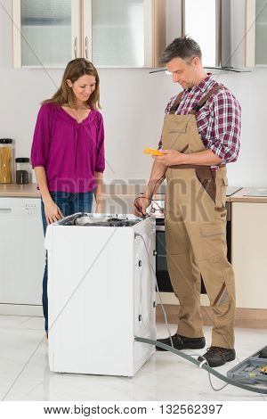 Woman Looking At Male Technician Checking Washing Machine In Kitchen