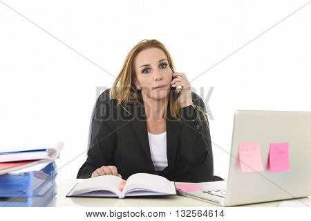 worried attractive businesswoman in stress working with laptop computer talking on mobile phone at office desk overwhelmed and overworked suffering collapse in frustrated face expression