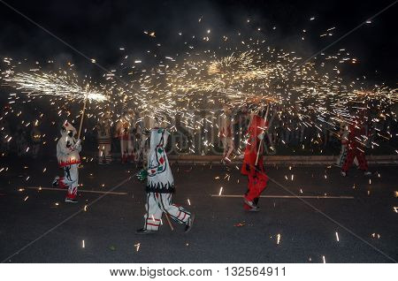 Traditional correfocs (fire runs) or Ball de Diables spectacle. Group of people dressed as devils and dancing with lighting fireworks fixed on devil's pitchforks. Reus Spain.