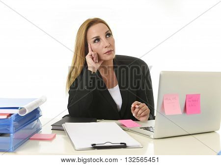 attractive 40s blond businesswoman working at office laptop computer sitting on the desk absent minded and thoughtful as if thinking of important business isolated on white background