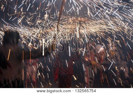 Traditional correfocs (fire runs) performance (Spanish: Baile de Diablos Catalan: Ball de Diables or Correfocs). Group of people dressed as devils and treading the streets letting off fireworks.