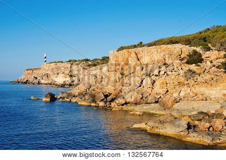 a view of the Mediterranean Sea, the Far des Moscarter lighthouse and a cliffy landscape of the northeastern coast of Ibiza Island, in the Balearic Islands, Spain