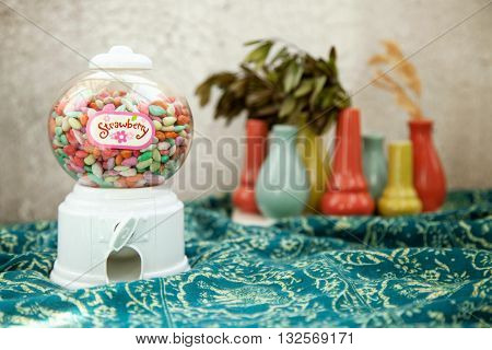 Round transparent bubble vending candy machine toy on a colorful background. Vintage warm colors