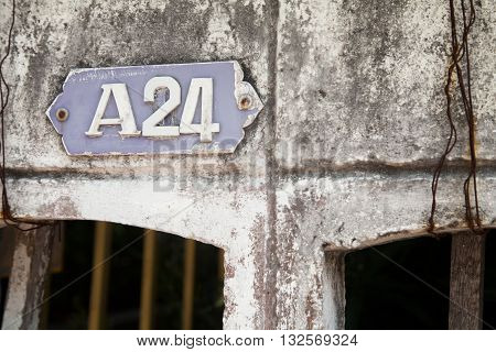 Old house number plate A 24 on a very shabby old wall. Number plaque. Building number sign