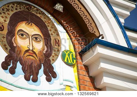 KHABAROVSK RUSSIA - JULY 23 2014: Contemporary Jesus Christ stone mosaic icon on an orthodox church. Sacred face on the wall colorful image close-up
