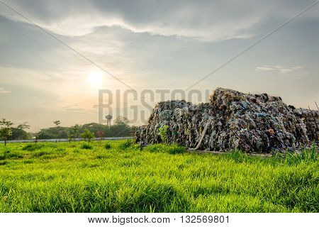 pyramid of garbage under the sun beam and wonderful green grass