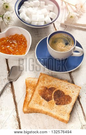 Breakfast, coffee, jam and toast with a heart pattern