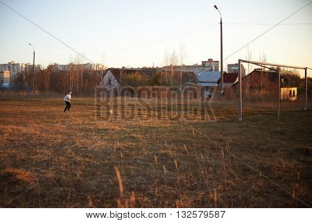 boy in pants, sneakers plays soccer, enjoys running, kicking the ball, smiling