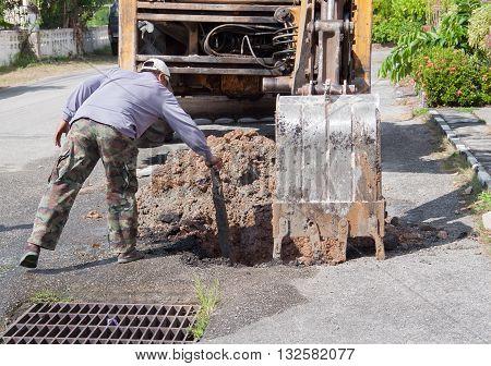 Plumbing Repair Man and excavator scoop digging, Repair of pipe water and sewerage on road, worker fixing broken water main.