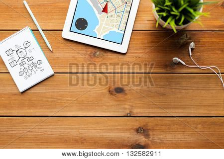 navigation, business and technology concept - close up of tablet pc computer with gps navigtor map on screen, notebook with scheme, pencil and earphones on wooden table