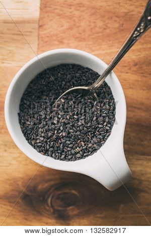 Black sesame seeds. Healthy sesame seeds in bowl  on wooden table. Top view.