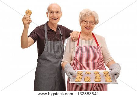 Elderly couple posing with a tray of homemade chocolate chip cookies isolated on white background