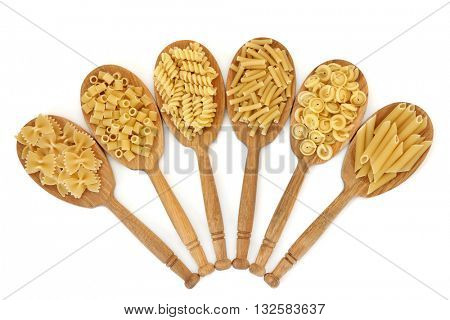 Pasta dried food in oak wood spoons over white background. Farfalle, ditali rigati, fusilli, macaroni, messicani and penne varieties from left to right.