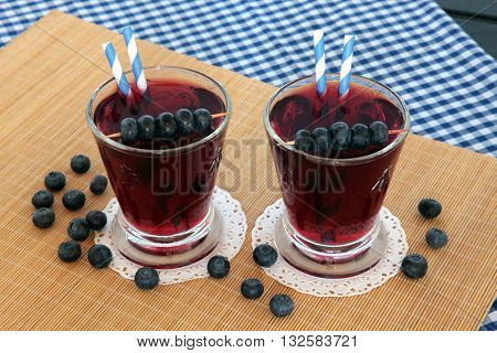 Blueberry juice health drink with fresh fruit on bamboo mat and blue check tablecloth background. High in vitamins, anthocyanins and antioxidants.