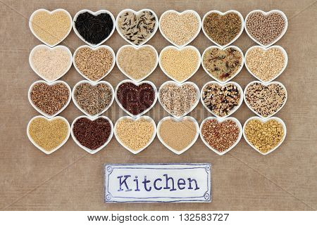 Healthy grain food selection in heart shaped porcelain bowls with old metal kitchen sign forming an abstract background.