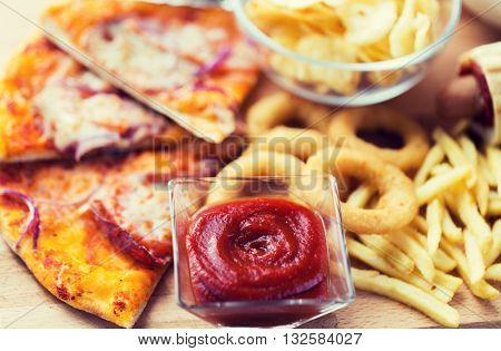 fast food and unhealthy eating concept - close up of ketchup in glass bowl over pizza, deep-fried squid rings, potato chips, peanuts and ketchup on wooden table